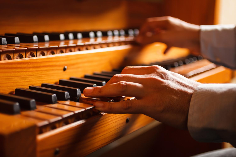 Detail of a man playing a church organ